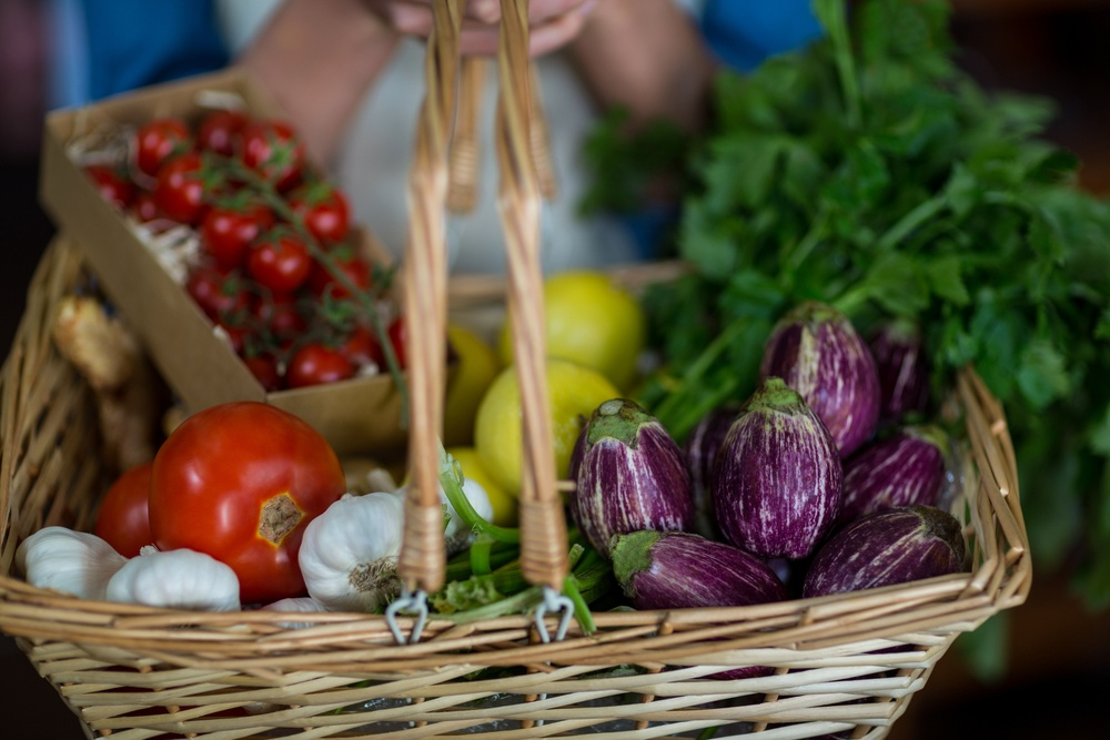 Close-up of female staff holding basket of vegetables in organic section of supermarket.jpeg