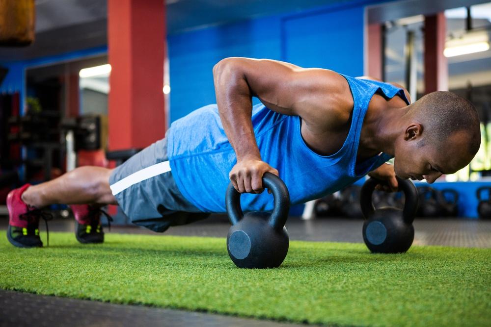 Full length of male athlete doing push-ups with kettlebells in fitness studio.jpeg